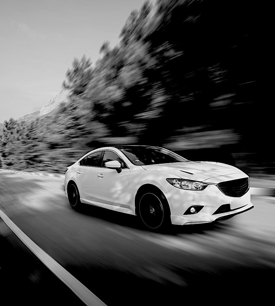White car speed driving on asphalt road at daytimeV