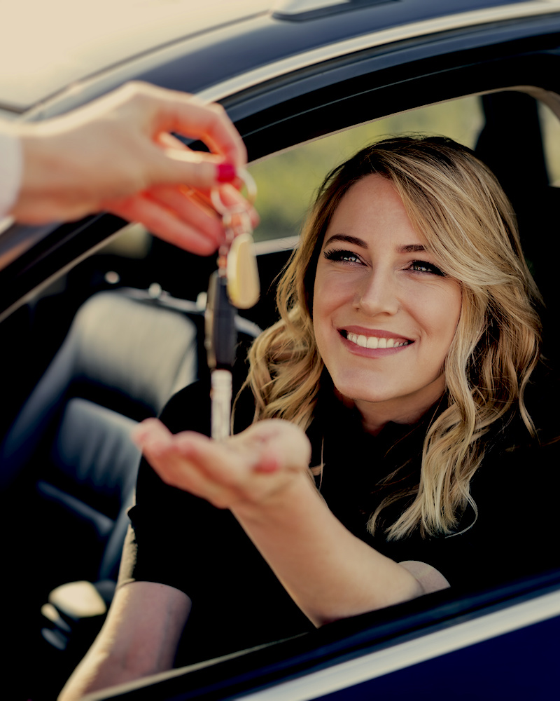 An attractive lady receiving keys to her car rental